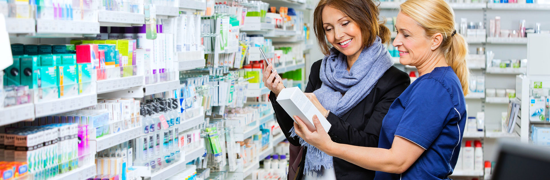 pharmacist and a customer looking at a medicine