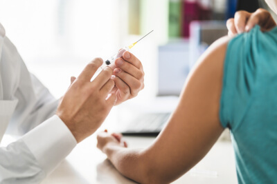 nurse giving vaccine shot in office room